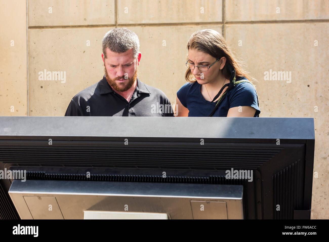 A couple read a stone tablet about the Oklahoma City bombing at the bombing memorial in Oklahoma City, Oklahoma, Stock Photo