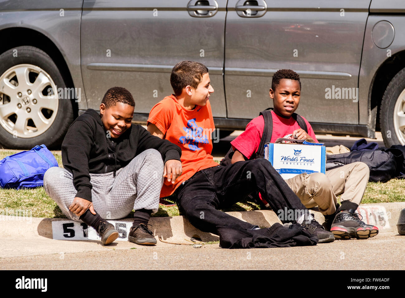 three laughing preteen boys sit on a neighborhood curb together in Oklahoma City, Oklahoma, USA. African American, - Stock Image