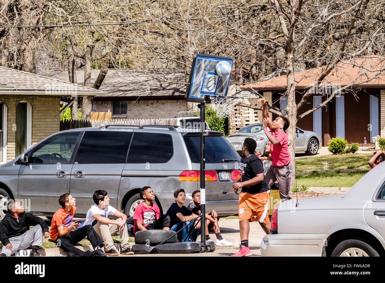 Teen and pre-teen boys gather and play basketball on the street in Oklahoma City, Oklahoma, USA. - Stock Image