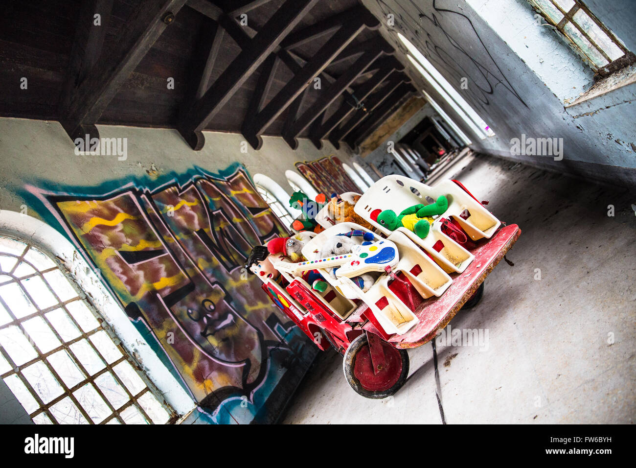 Orangeburg, New York, USA - February 17, 2016: Eerie scene with cart full of toys  inside abandoned children's - Stock Image