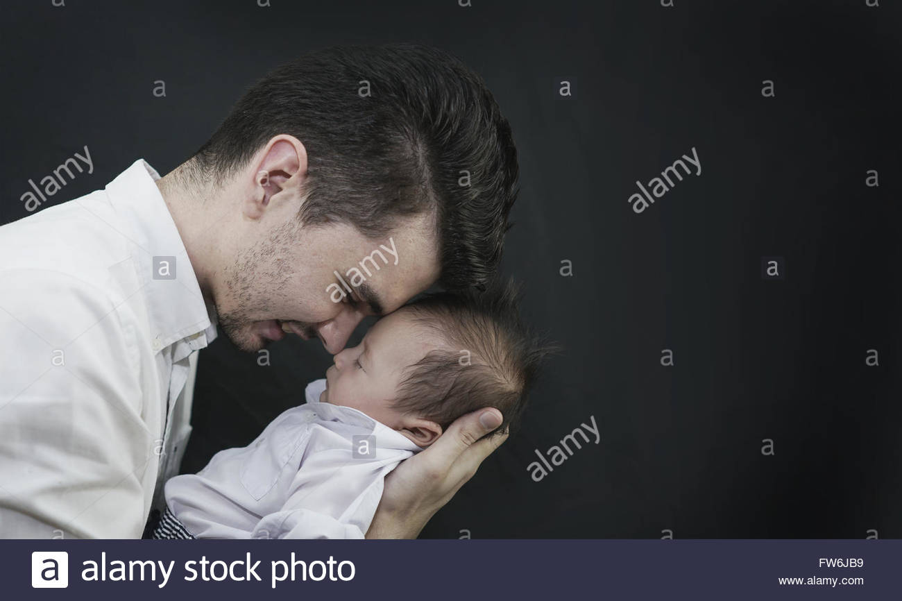 Baby Boy in Dad's Hands Black Background - Stock Image