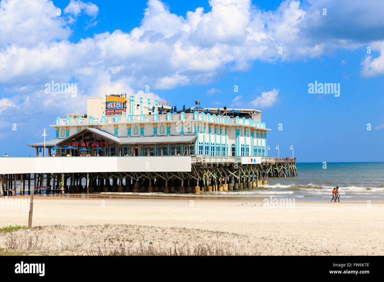 Daytona beach with tourists and sunbathers, Florida, America, USA and the traditional pier in the background. - Stock Image