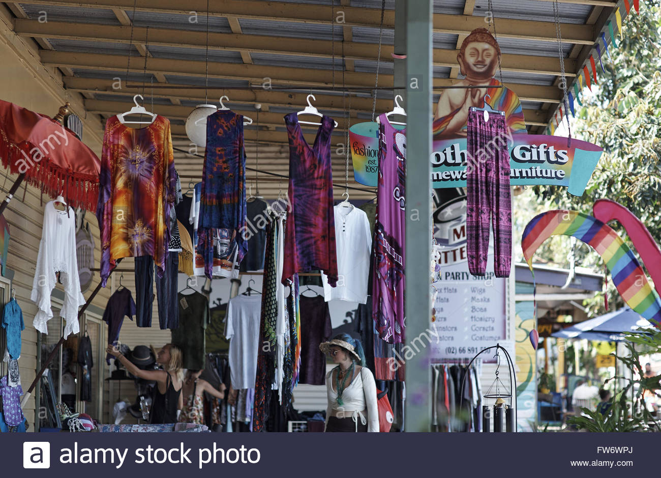 Young women browse through clothes hanging on the footpath, outside the 'Mad Hattery' store; in the main - Stock Image