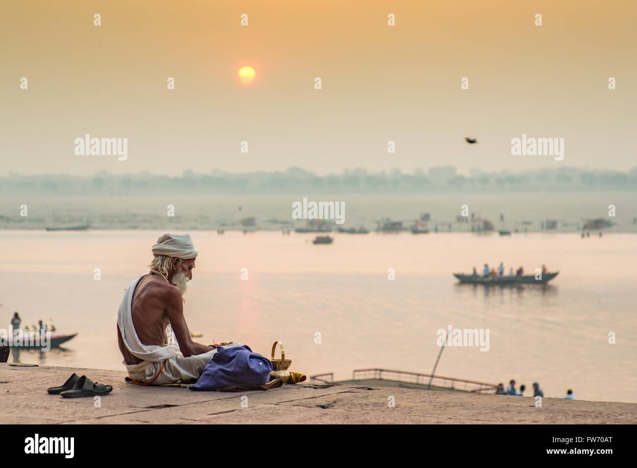 A Sadhu (Hindu religious devotee) is sitting by the holy river Ganges in Varanasi as the sun rises in the background. - Stock Image