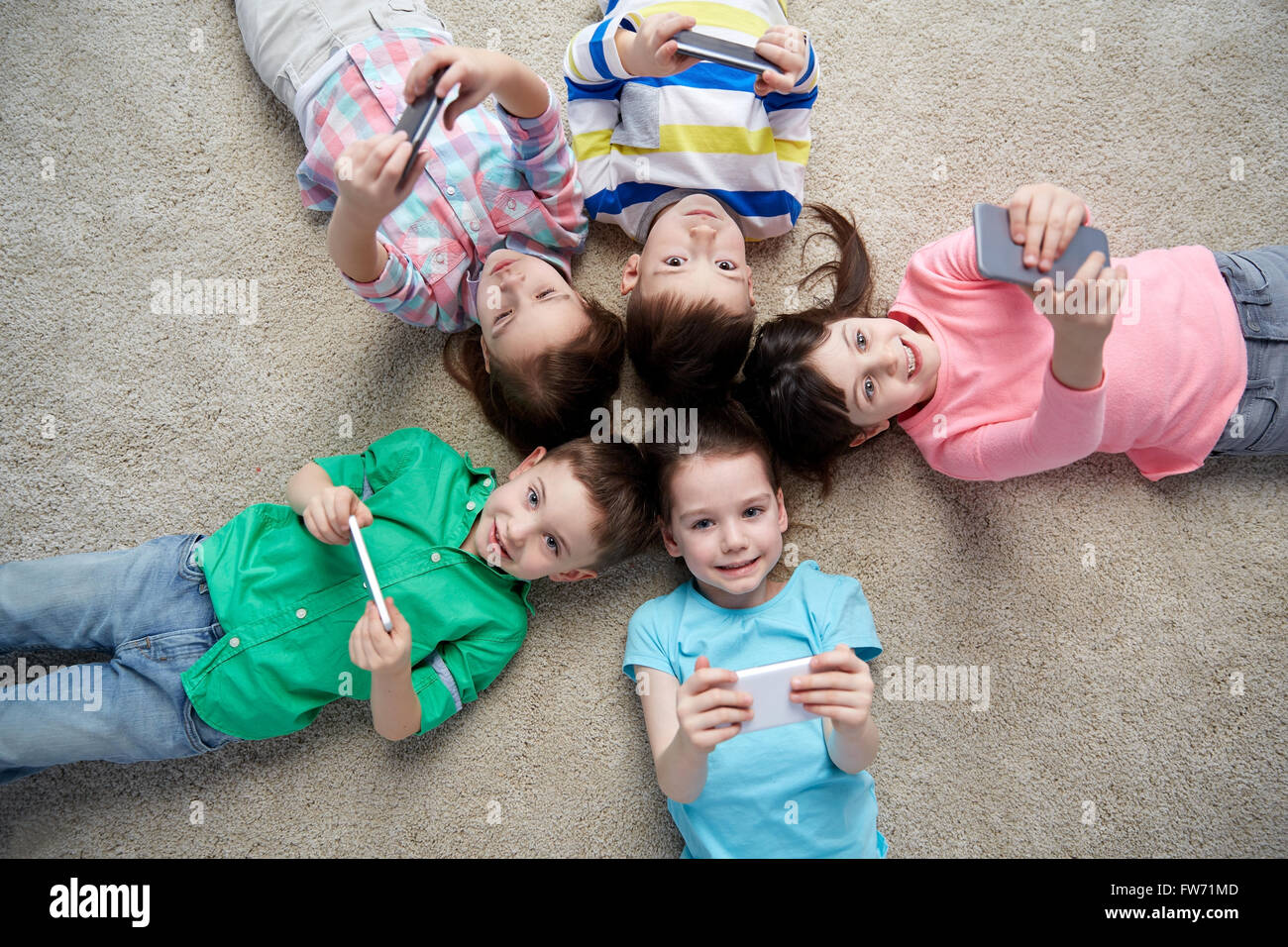 happy children with smartphones lying on floor - Stock Image