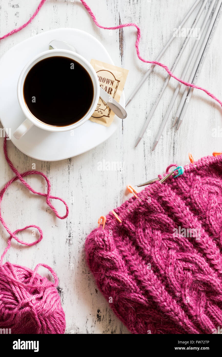 Lazy afternoon and relaxing knitting with a cup of coffee. - Stock Image