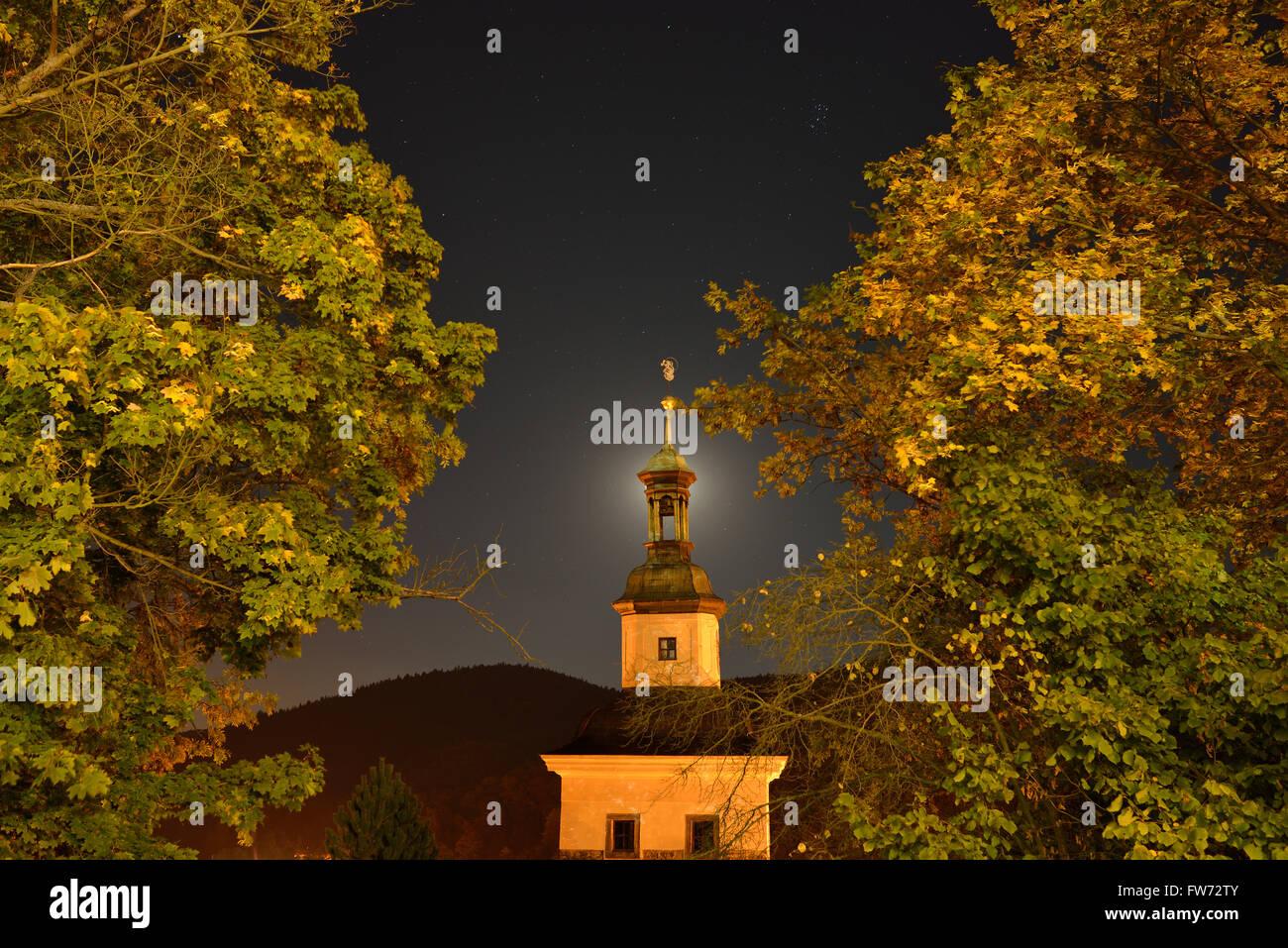 CHURCH AND FOLIAGE ILLUMINATED BY STREET LIGHTS WITH MOON BEHIND STEEPLE. Loket, Bohemia, Czech Republic. - Stock Image
