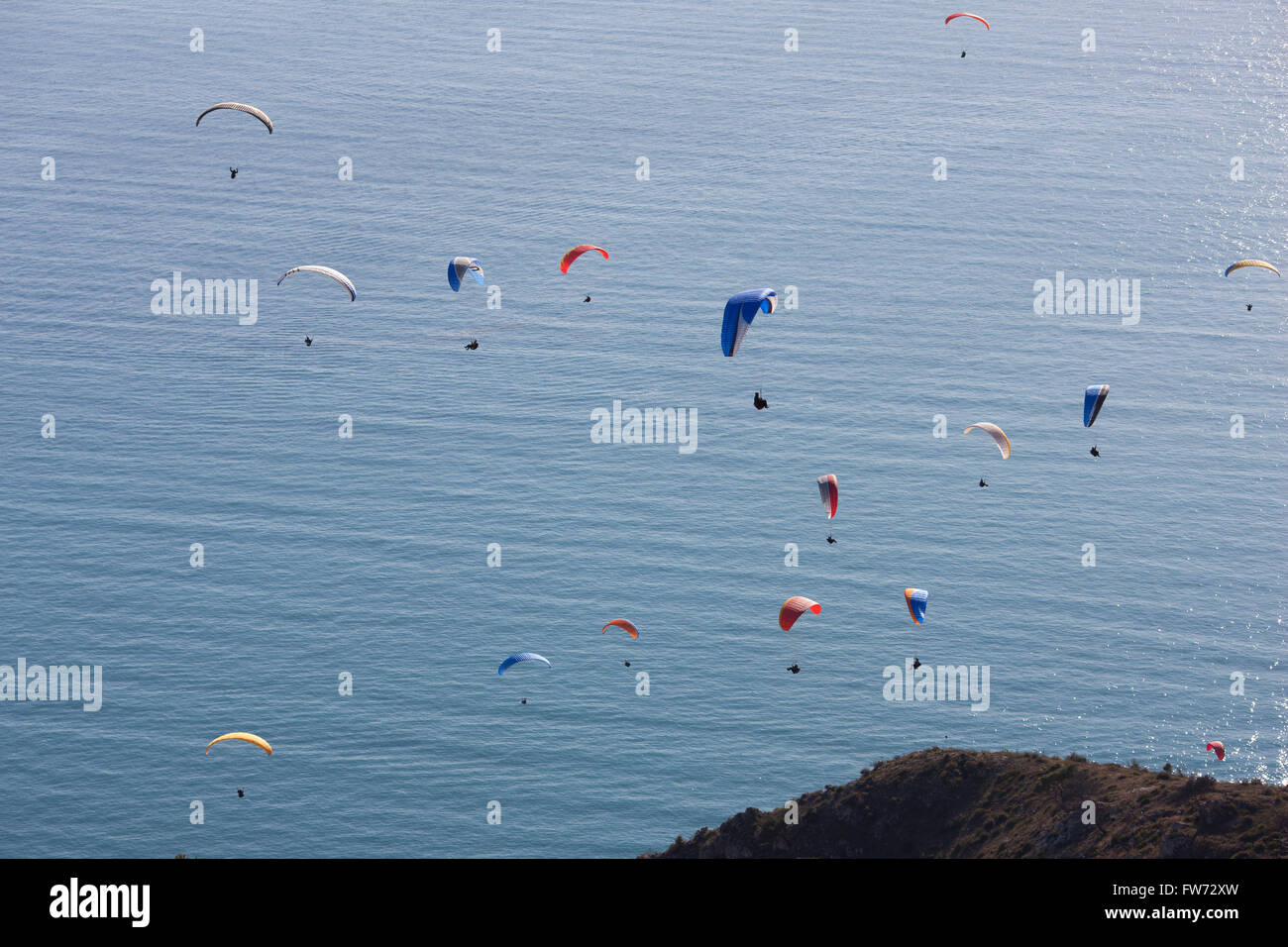 PARAGLIDERS SOARING OVER THE MEDITERRANEAN. Paragliders over the French Riviera, in Roquebrune-Cap-Martin, France. - Stock Image