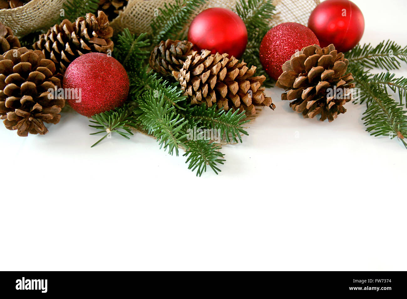 Red Christmas Tree ornaments, pine cones, evergreen branches, and ...