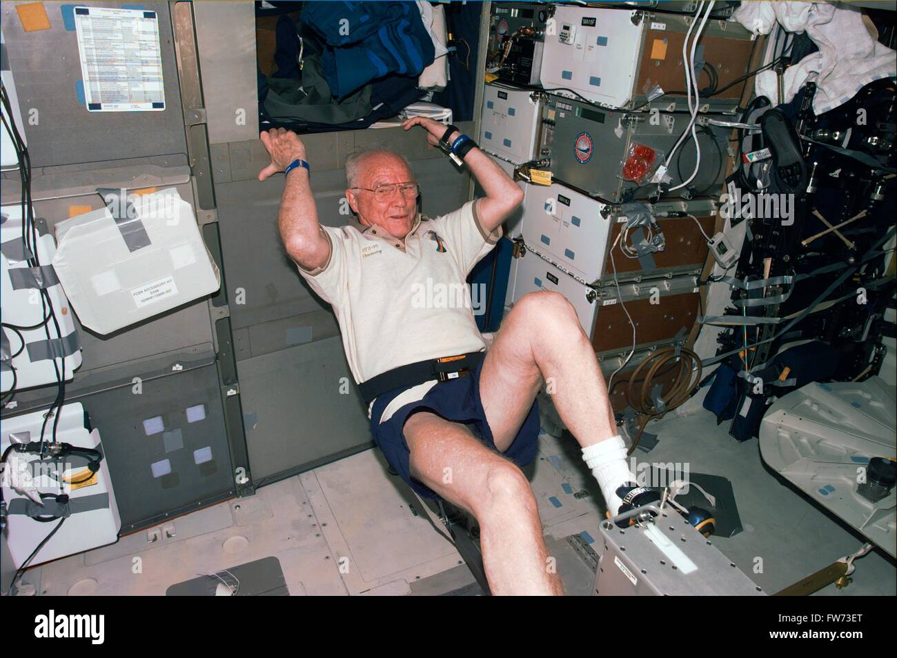 Space Shuttle Discovery STS-95 astronaut and Senator John Glenn works out on the ergometer device during flight - Stock Image