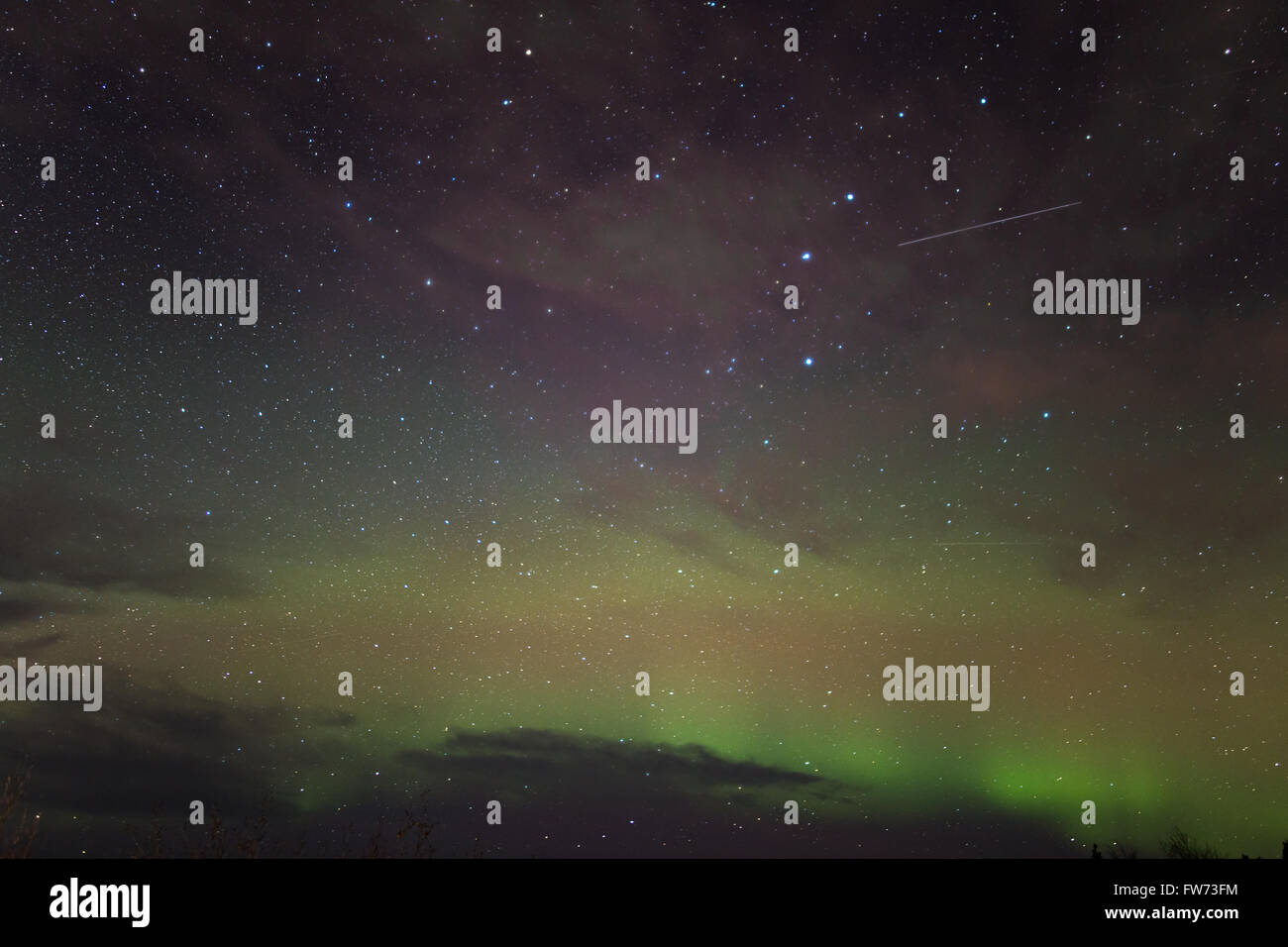 Satellites, and stars, and the northern lights (aurora borealis) put on a show in the sky over Fairbanks, Alaska - Stock Image