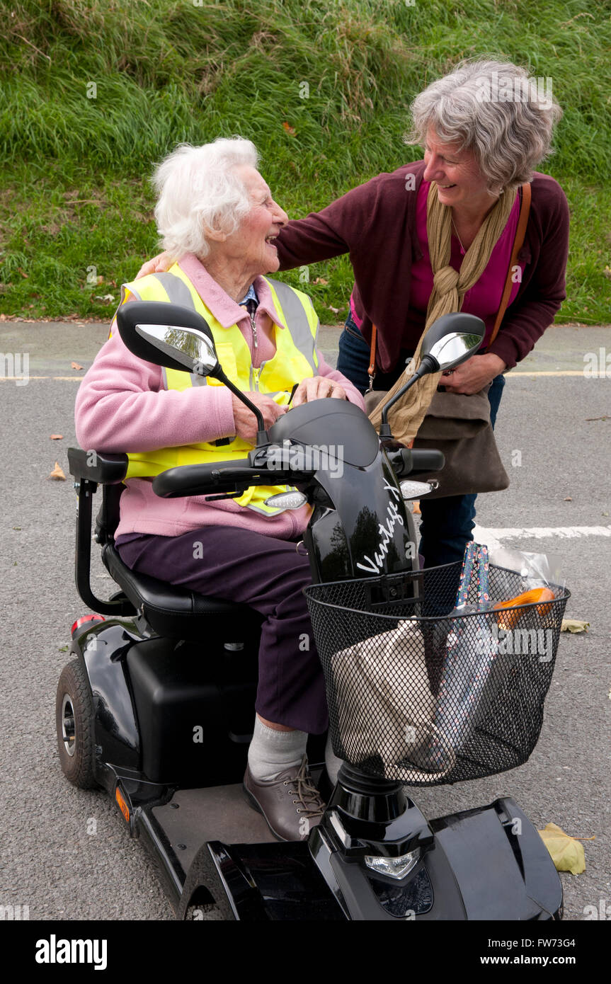 Elderly woman sitting in her mobility scooter talking to her carer - Stock Image