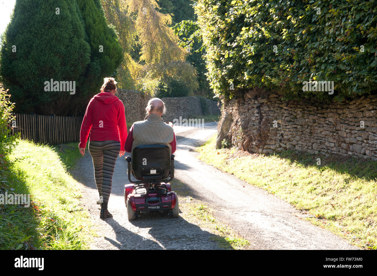 Rear view of an elderly man using a mobility scooter with his carer walking beside him - Stock Image