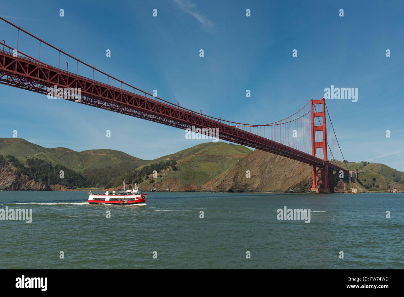The Golden Gate Bridge with sightseeing boat passing underneath it, near San Francisco, California, USA - Stock Image
