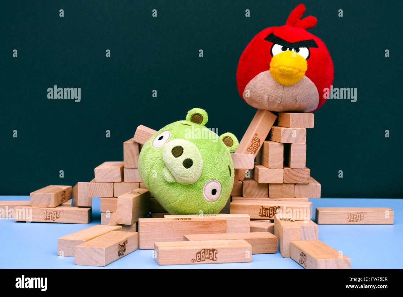 Angry Bird vs. Bad Piggies. Red bird broke bad pig's house. Bad piggy lying in pile of Jenga bricks which its house - Stock Image
