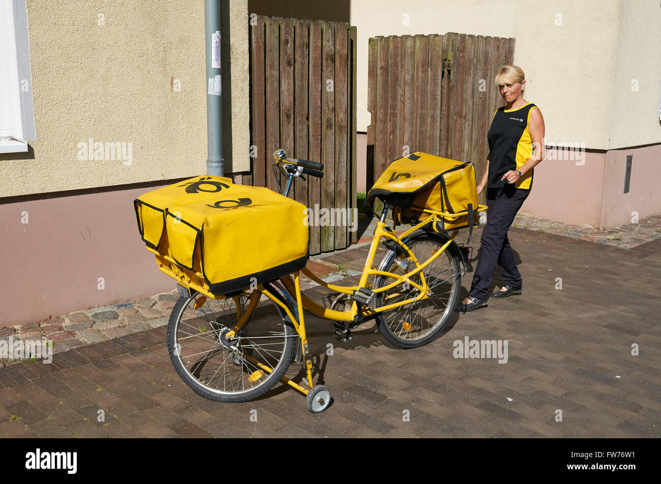 STRALSUND, GERMANY - AUGUST 13, 2015: The postwoman with his yellow bike delivers the mail - Stock Image