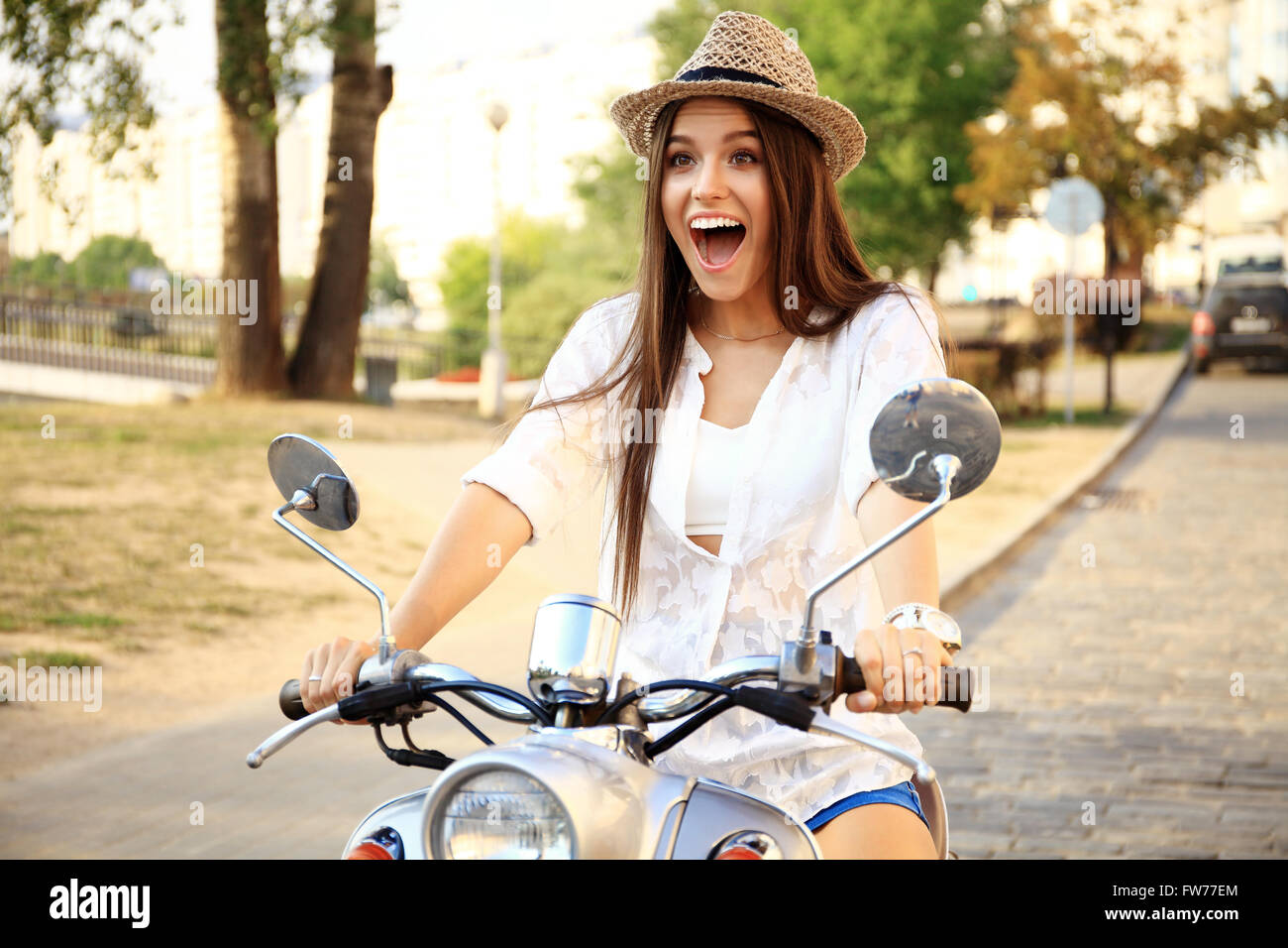 Portrait of a beautiful girl sitting on silver retro scooter, smiling and looking at the camera - Stock Image