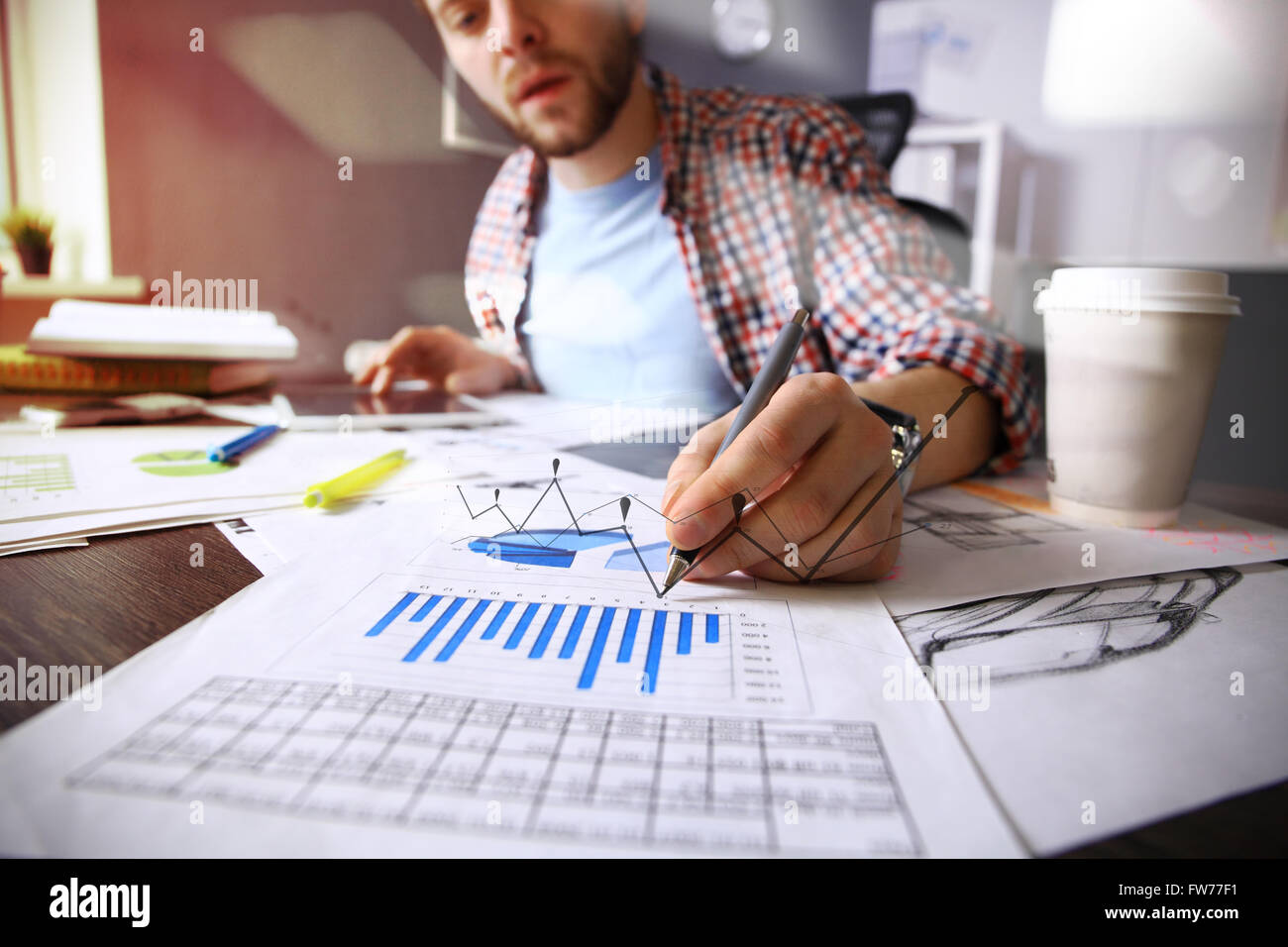 business documents on office table with smart phone and digital tablet and graph business with social network diagram - Stock Image