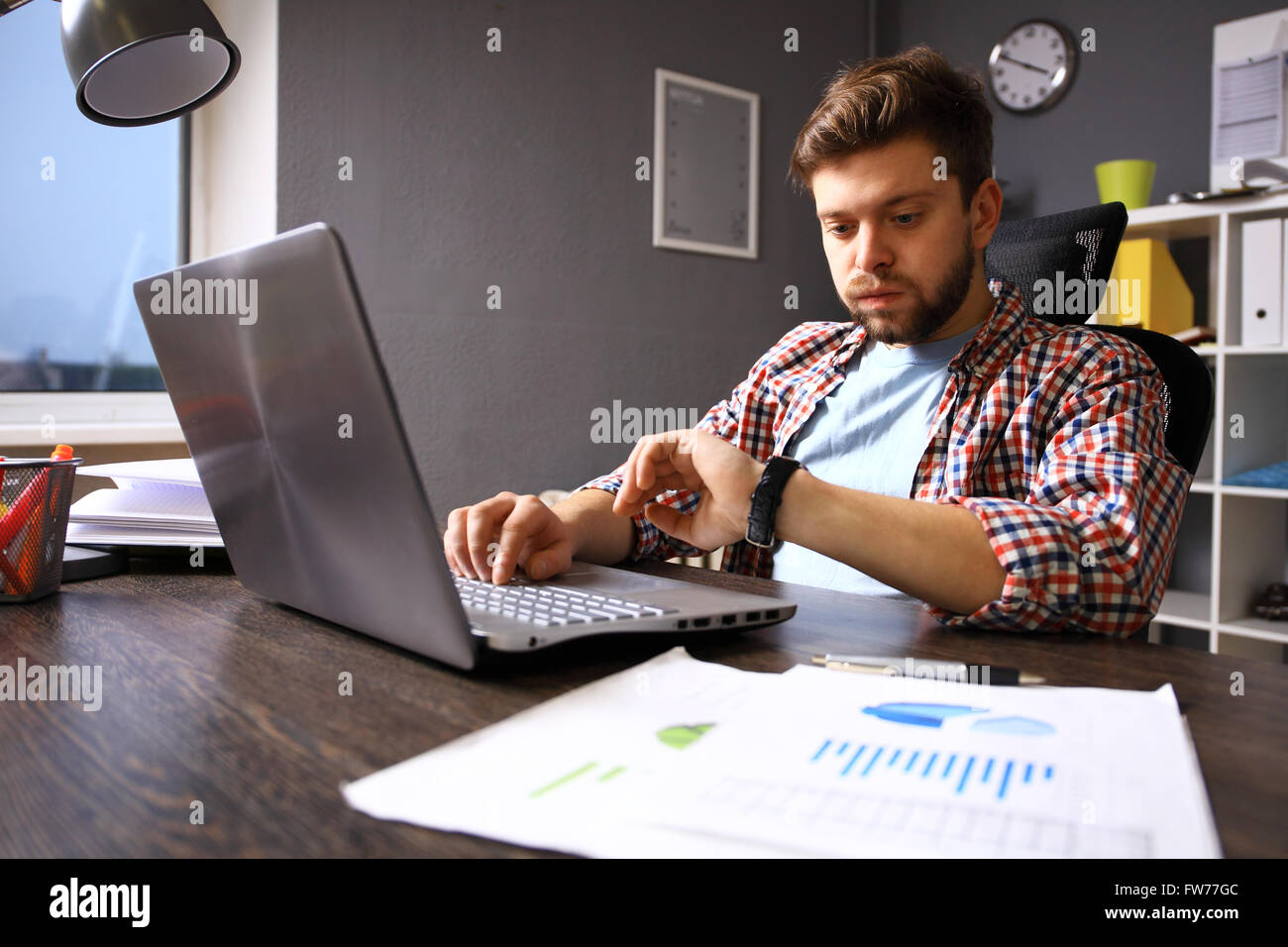 Business and time management concept. Stressed business man looking at wrist watch. Human emotion - Stock Image