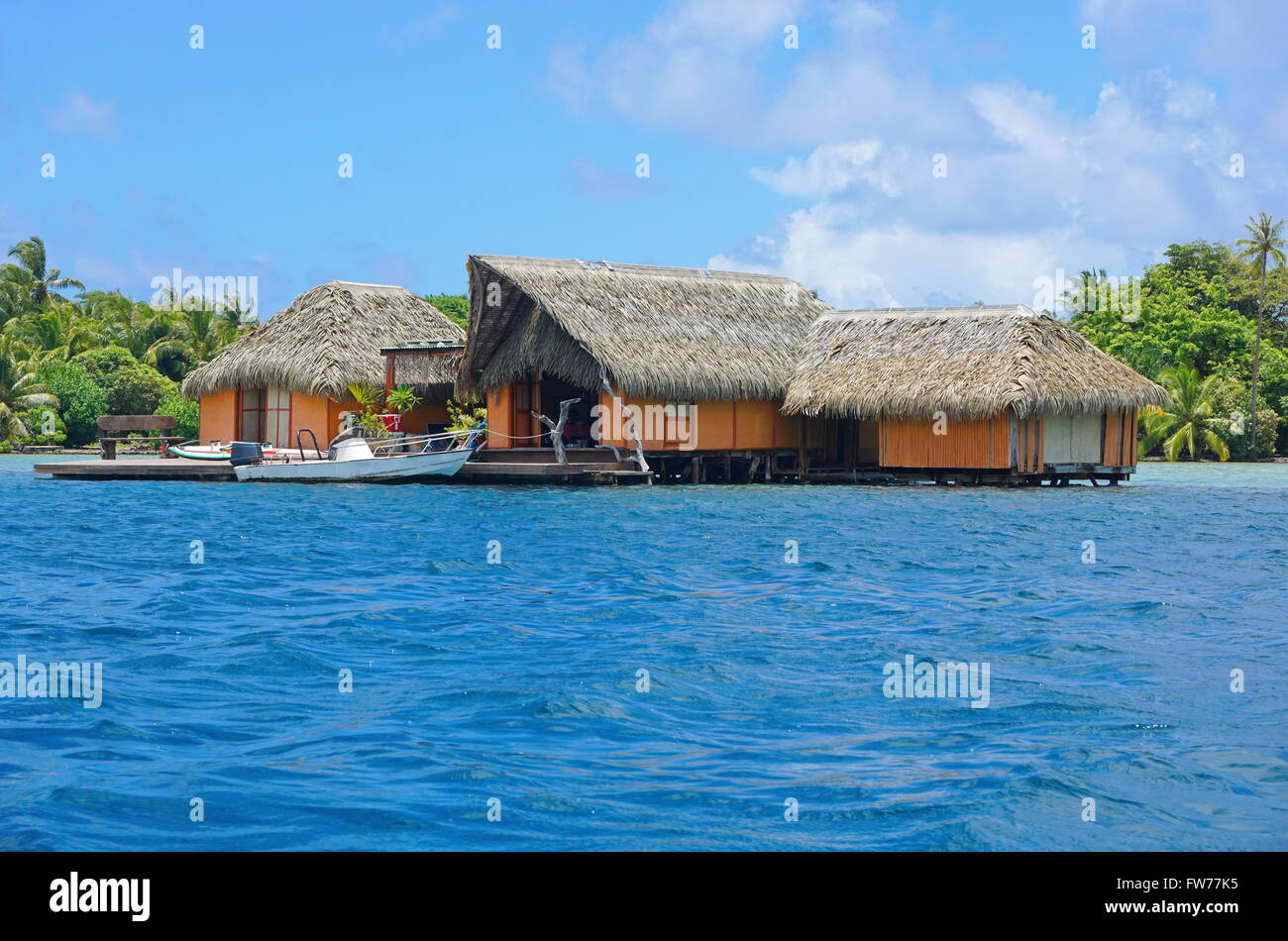 tropical-home-over-water-with-thatched-roof-and-a-boat-at-dock-huahine-FW77K5.jpg