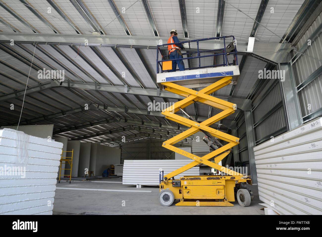 A builder works from the cage on a scissor lift while attaching
