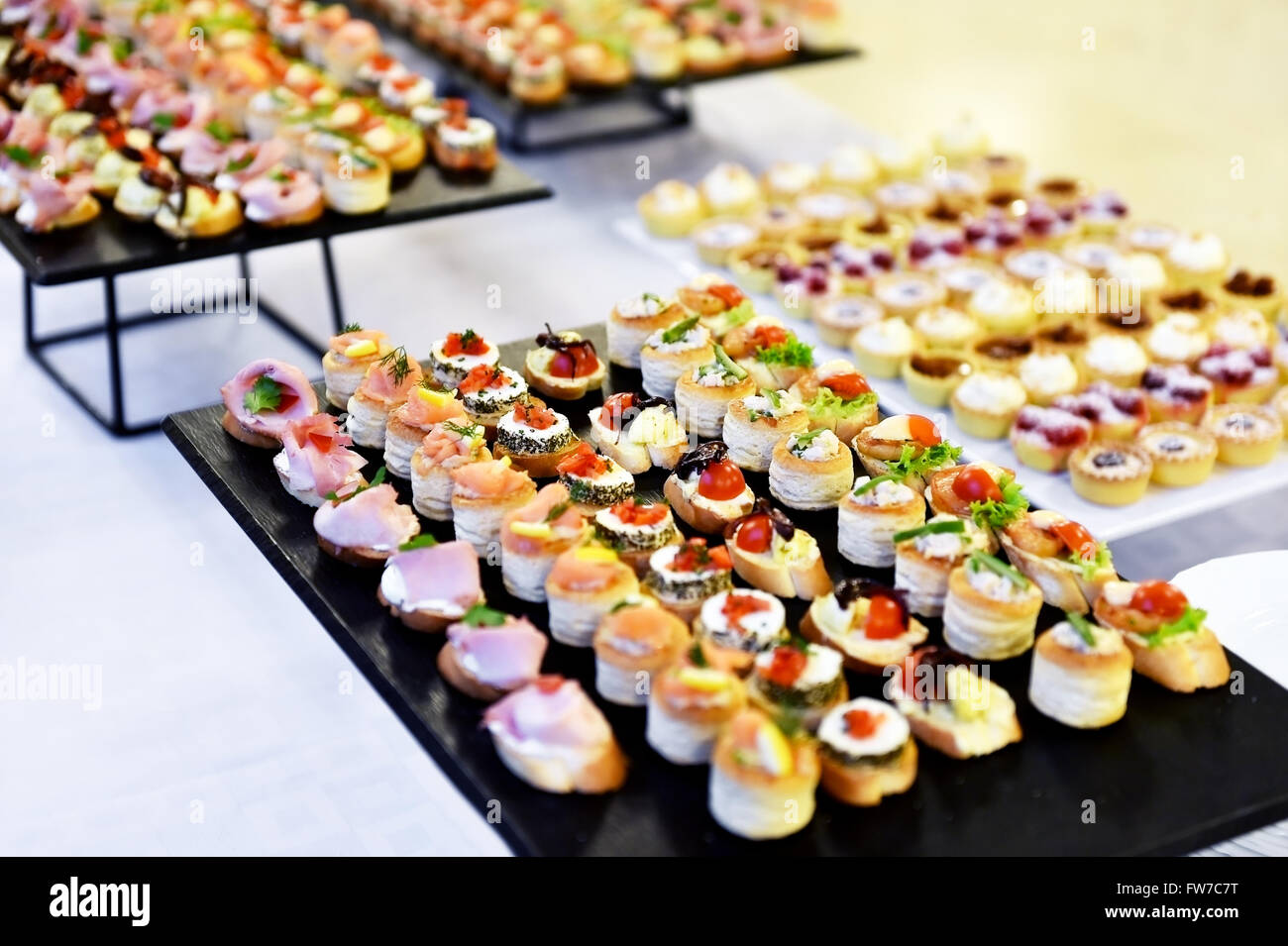 Catering food shot with small appetizers on plates ready for eat - Stock Image