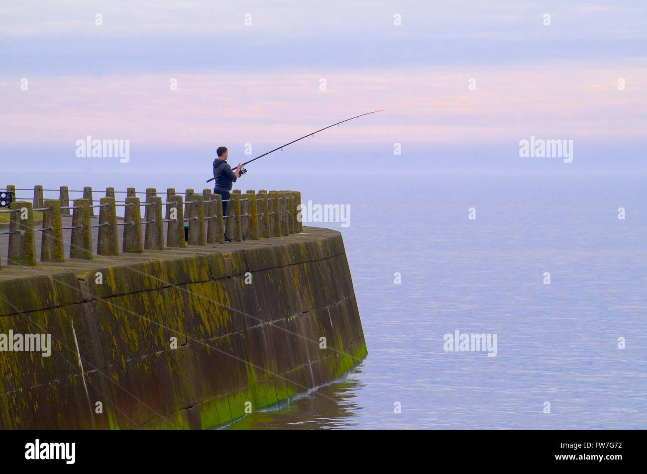 Sea fisherman fishing of the sea wall. Evening. Silloth, Cumbria, England, United Kingdom, Europe. - Stock Image