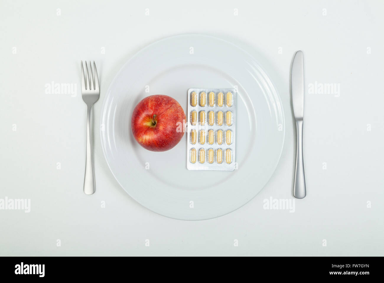 Red apple and vitamin pills - Stock Image