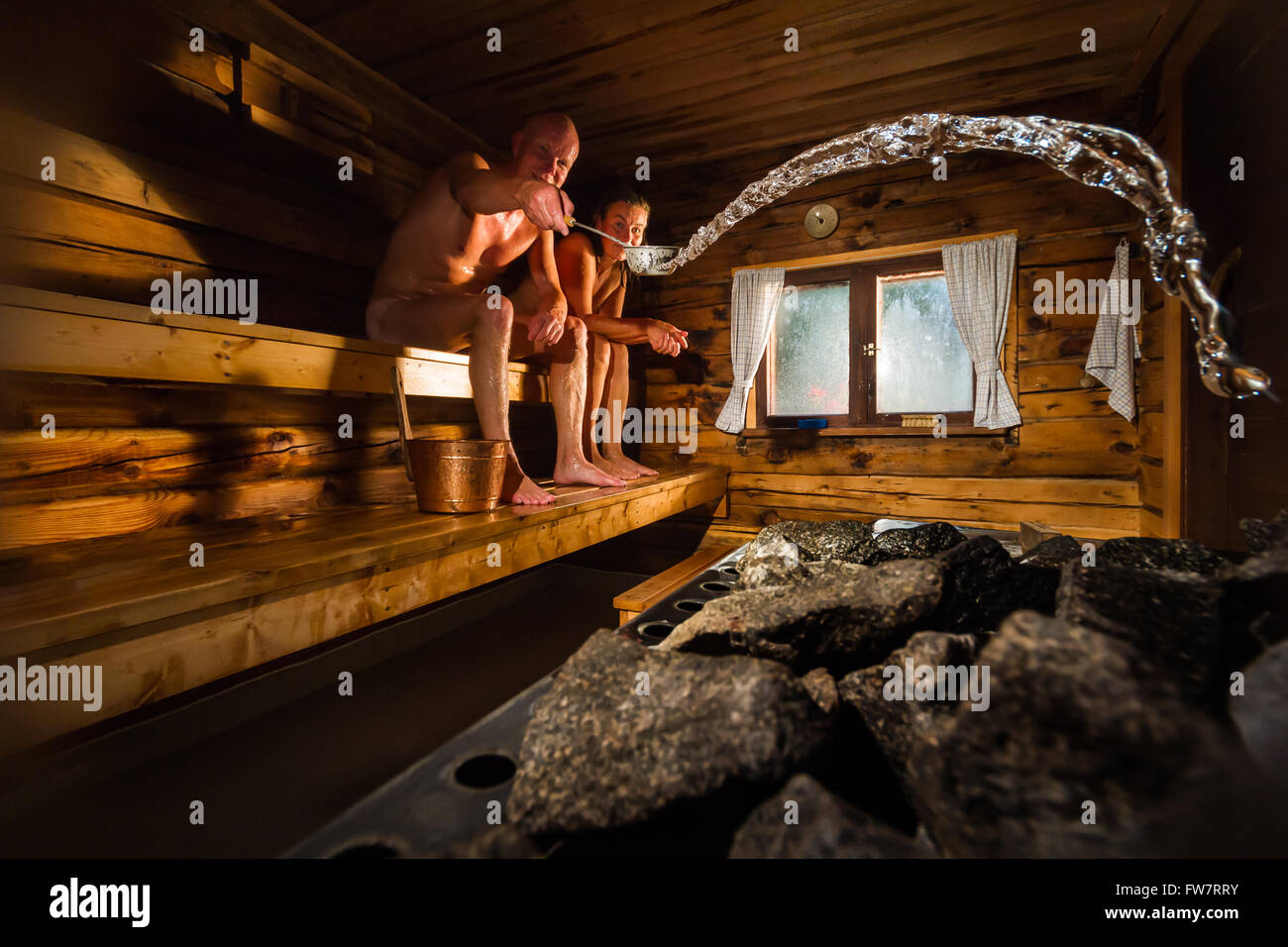 Middle aged couple in traditional wooden Finnish sauna, man throwing water to hot stove - Stock Image
