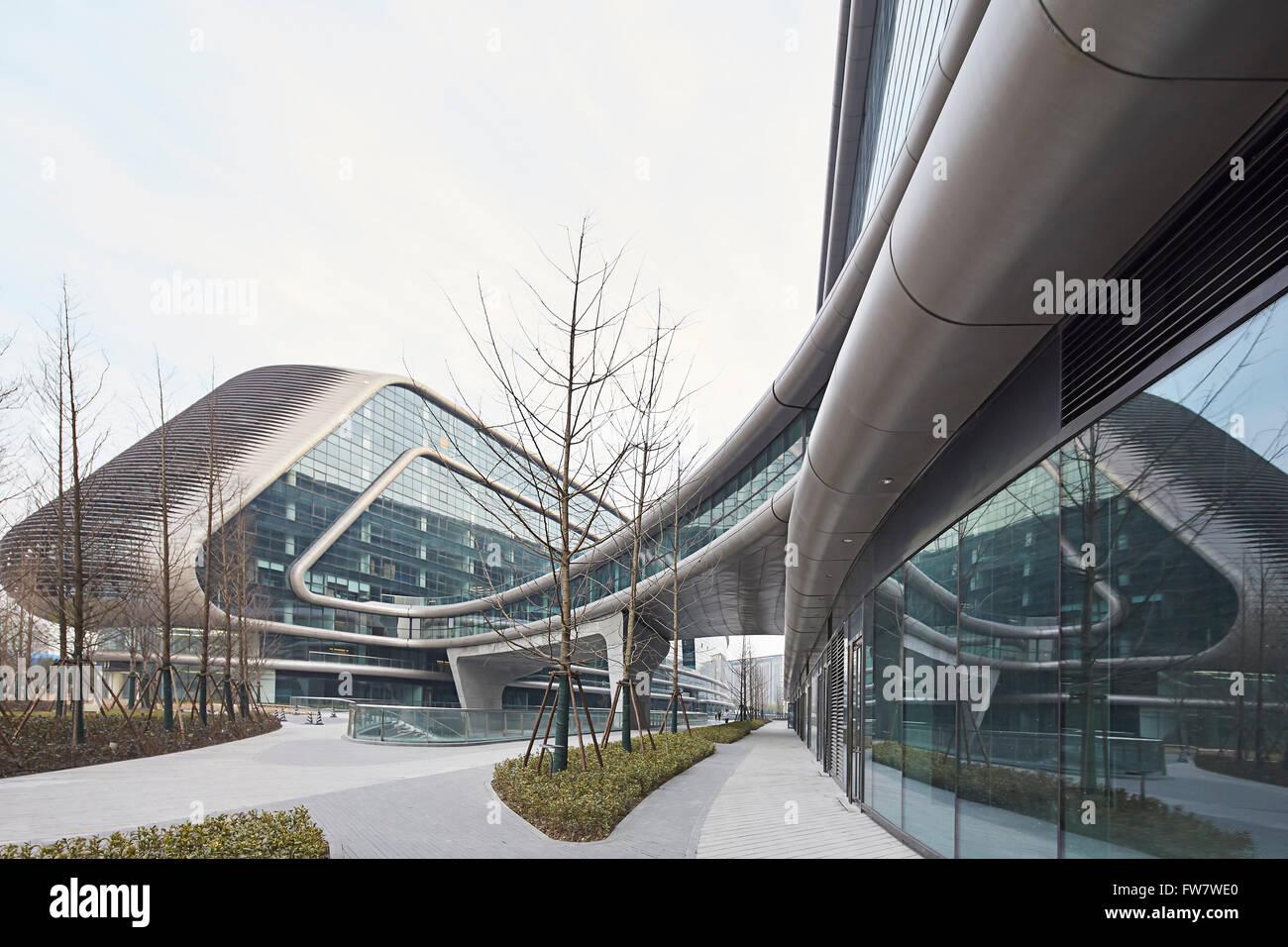 Glass curtain wall of exterior facade and landscaped walkways. Sky SOHO, Shanghai, China. Architect: Zaha Hadid Stock Photo