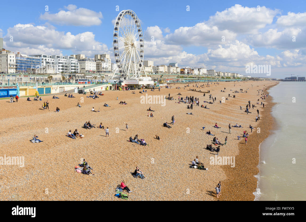 People on the Brighton beach on a sunny day in early Spring, in Brighton, East Sussex, England, UK. - Stock Image