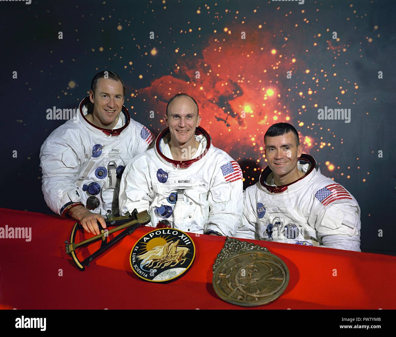 Apollo 13 prime crew pose together in their spacesuits with a model of a sextant, the Apollo 13 insignia, and a - Stock Image