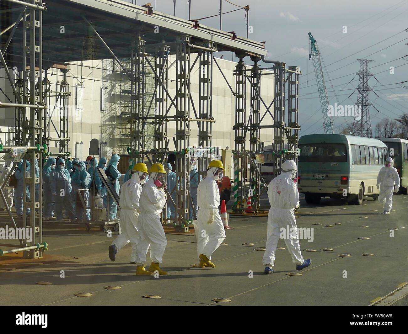 Workers in protective clothing and masks outside the Emergency Response Centre at the Fukushima Daiichi Nuclear - Stock Image