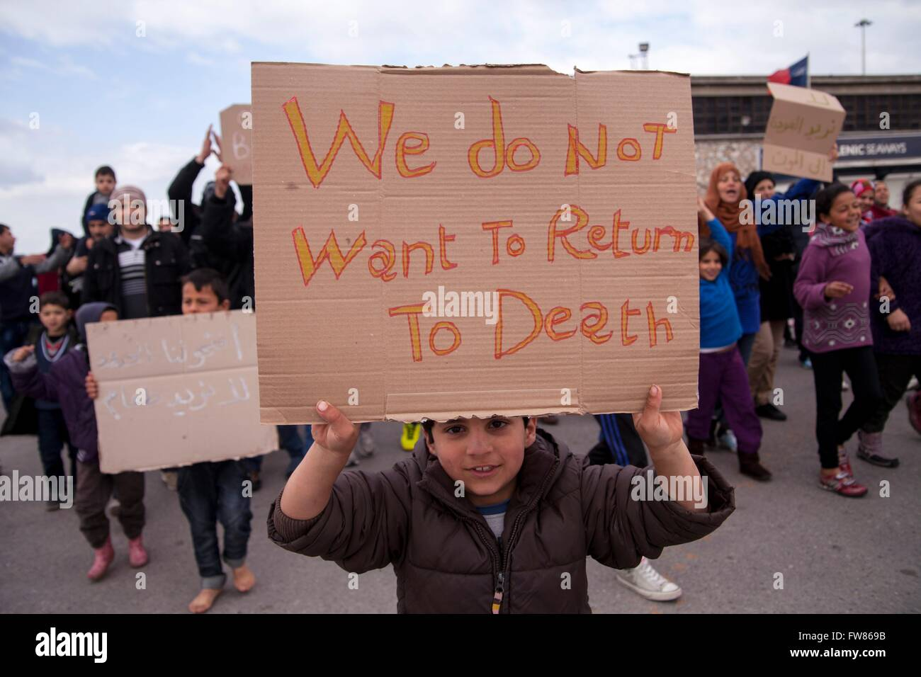 Syrian refugees at habour of Piraeus. Sing 'We don_t want to return to death'. Refugees demand opening of - Stock Image