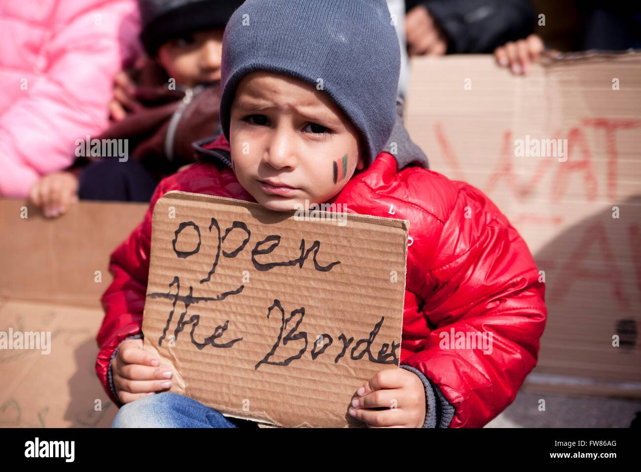 Afghan refugee child at habour of Piraeus. Refugee with sign 'Open the border', demanding opening of Greek - Stock Image