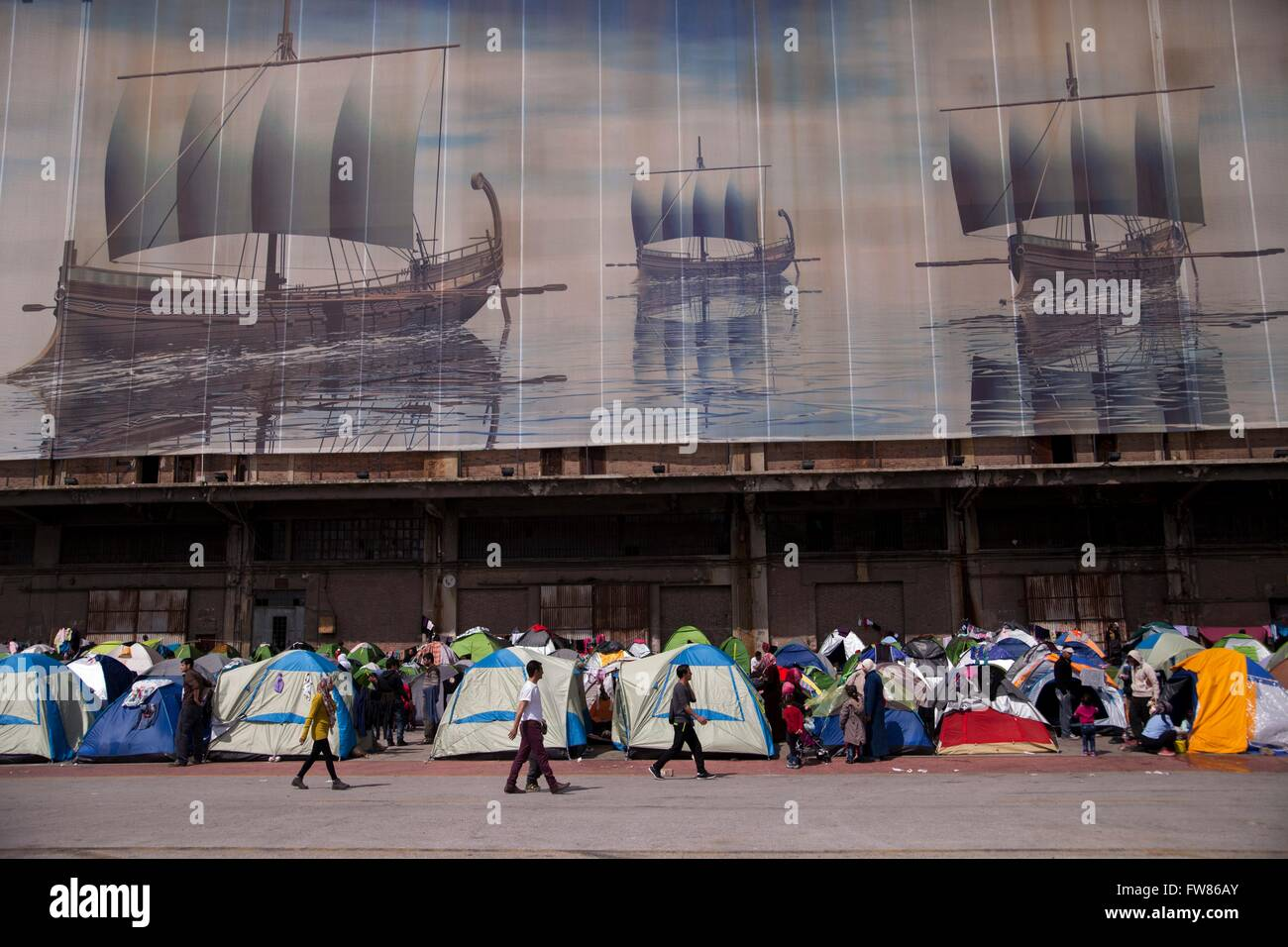 Image with sailing boats, above tens of refugees, at habour of Piraeu. For weeks thousands of refugees are stuck - Stock Image