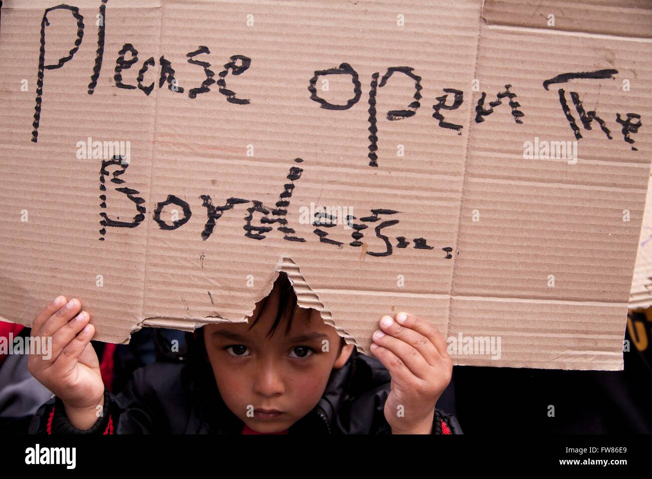 Afghan refugee child at habour of Piraeus. Refugee with sign 'Please open the border', demanding opening - Stock Image