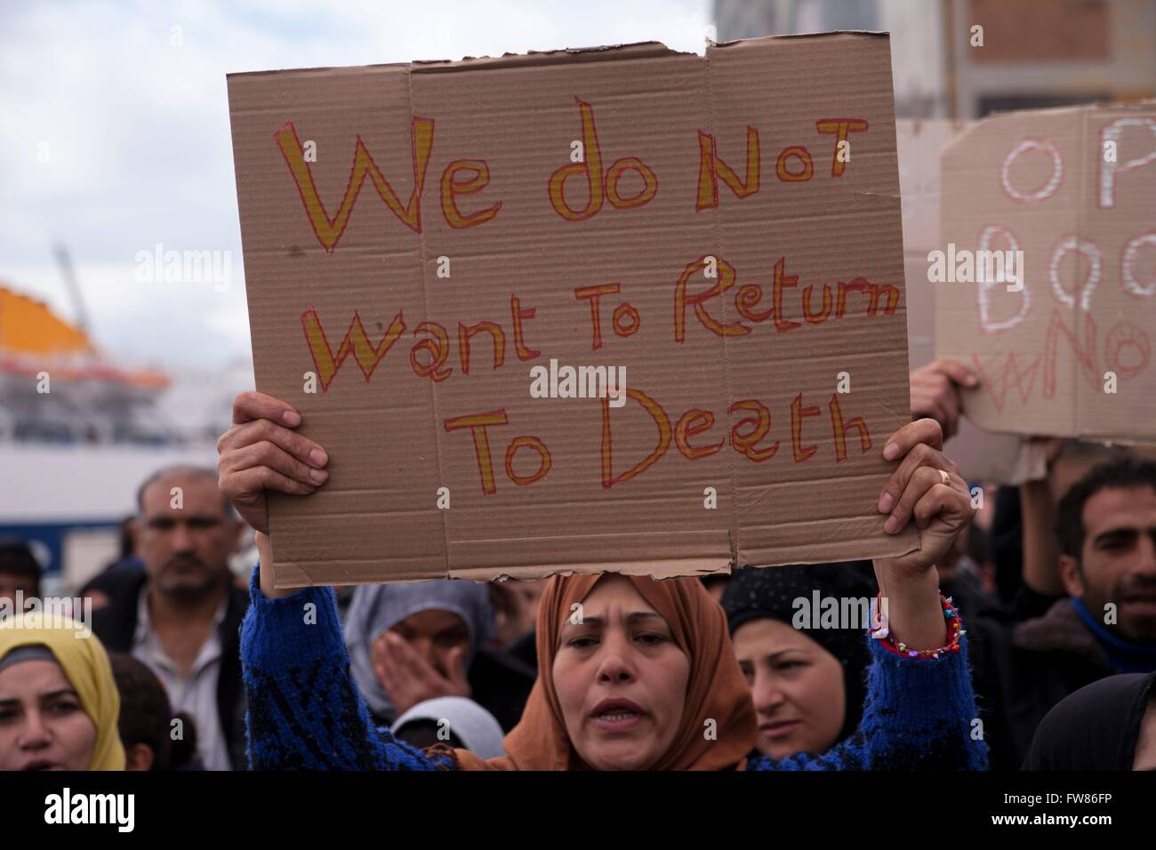 Afghan refugees at habour of Piraeus. Sing 'We don_t want to return to death'. Refugees demand opening of - Stock Image
