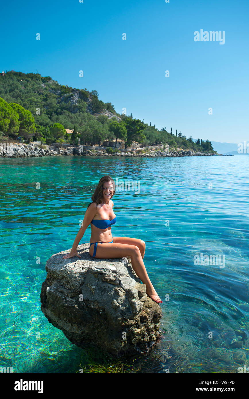 young woman on rock nissaki beach corfu greece stock photo