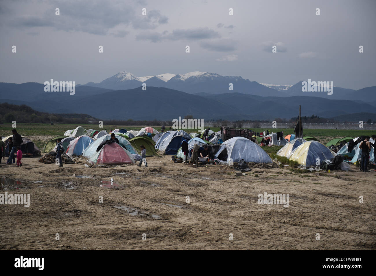 Stranded people stand in front of their tents, as refugees and migrants remain stranded at the closed Greek Macedonian - Stock Image