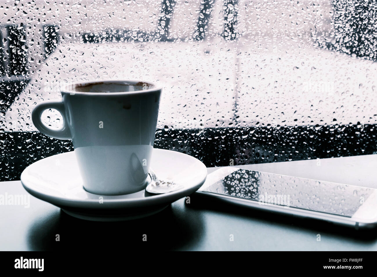 closeup of a cup of coffee and a smartphone on a table while is raining outside - Stock Image