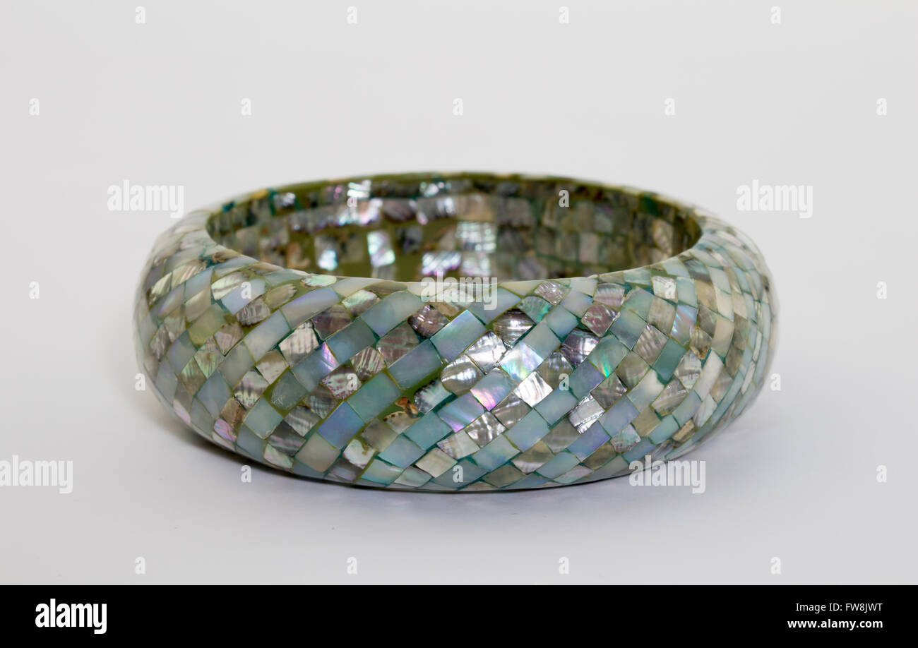 Focus on front of blue mother of pearl bangle isolated on white - Stock Image