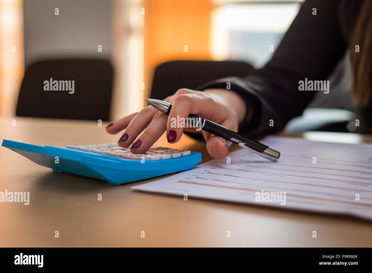 Business woman calculating an invoice in her office - Stock Image