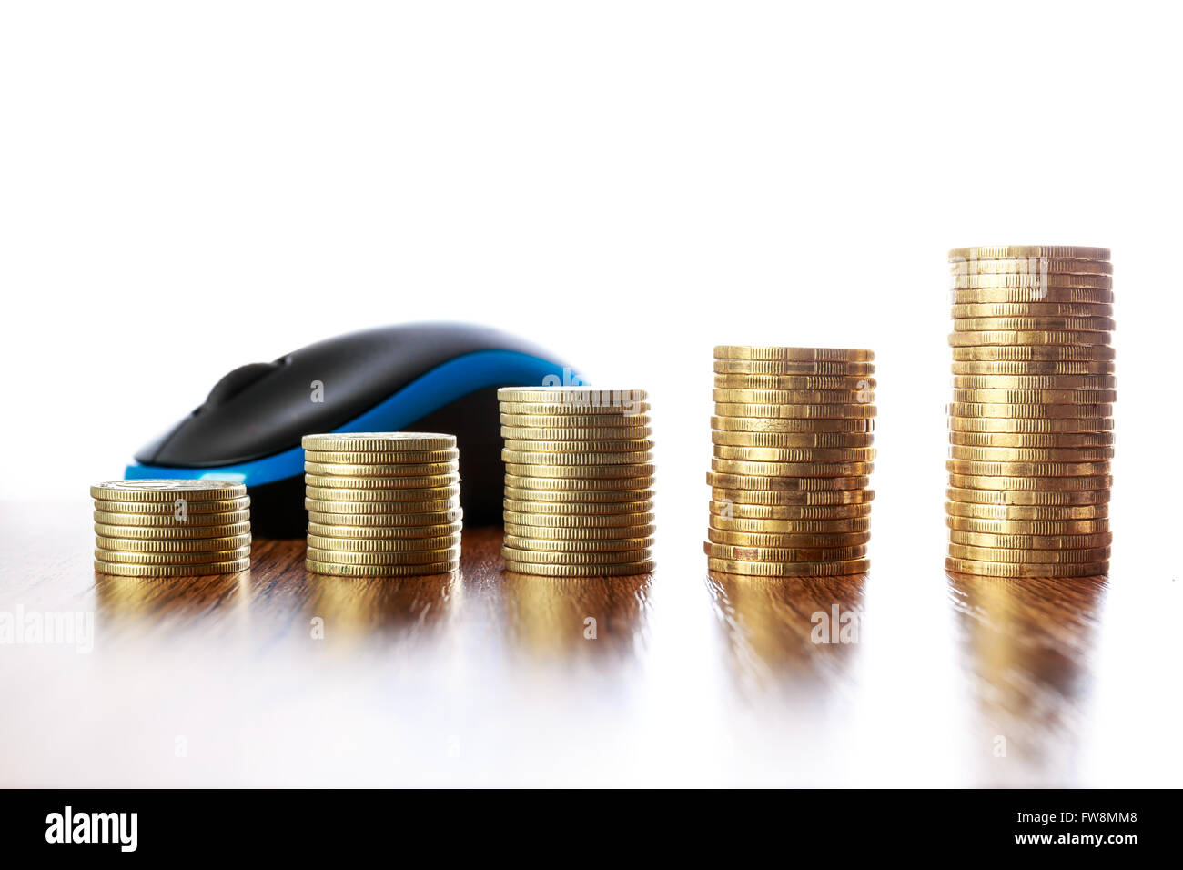 Towers of coins on wooden table in front of computer mouse - Stock Image