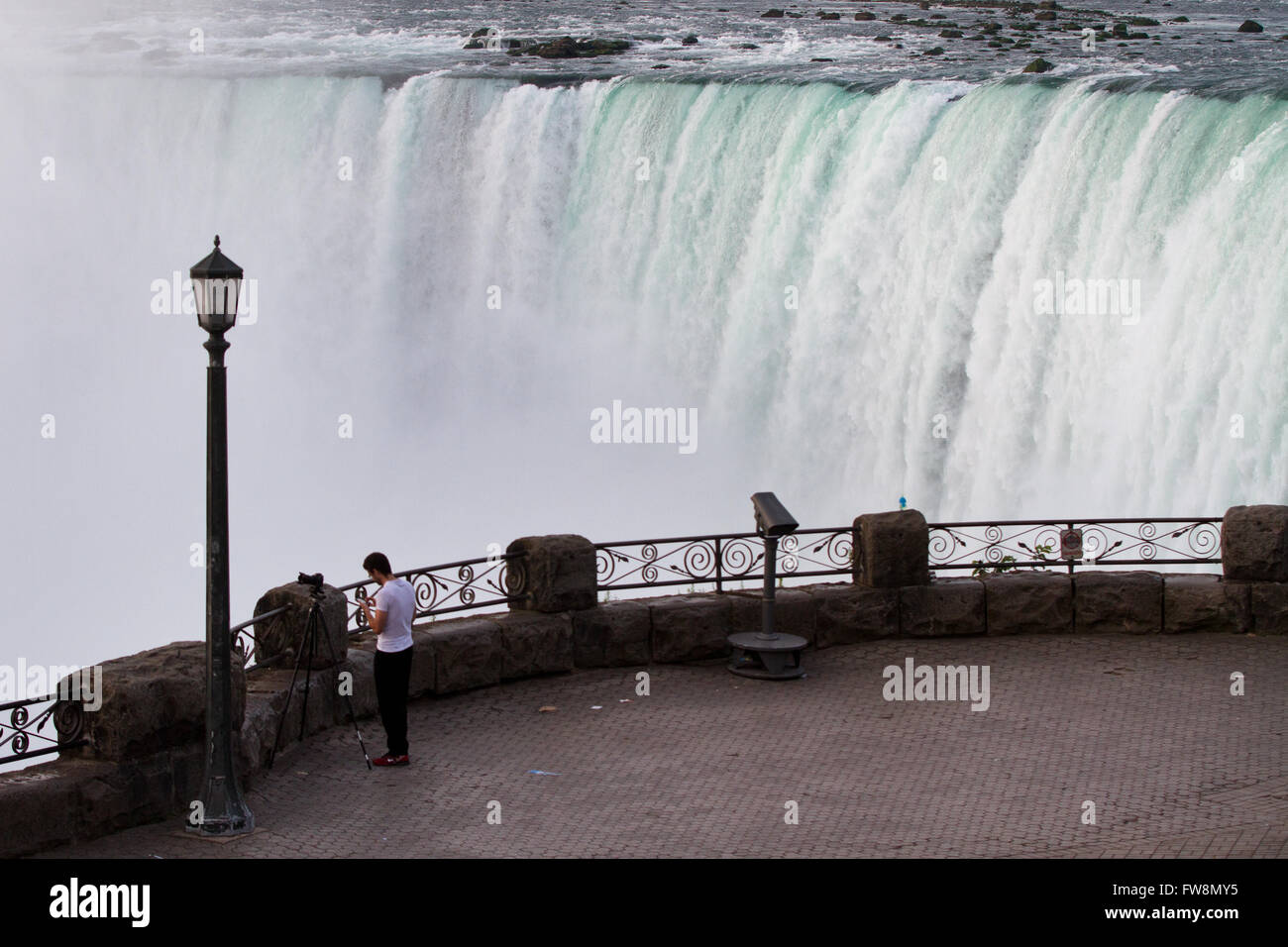 A tourist takes pictures of the Canadian Horseshoe falls early in the morning in Niagara Falls Ont., on Tuesday - Stock Image