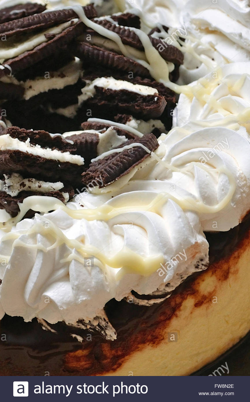 Close-up of a cookies and cream chocolate marble cheesecake. There's also melted white chocolate drizzled on - Stock Image
