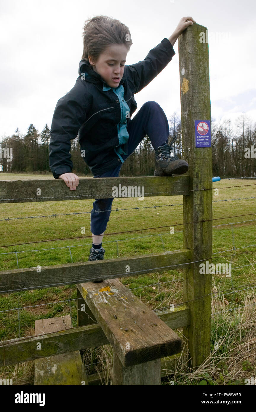 A young boy on a country walk climbing over a new style ...