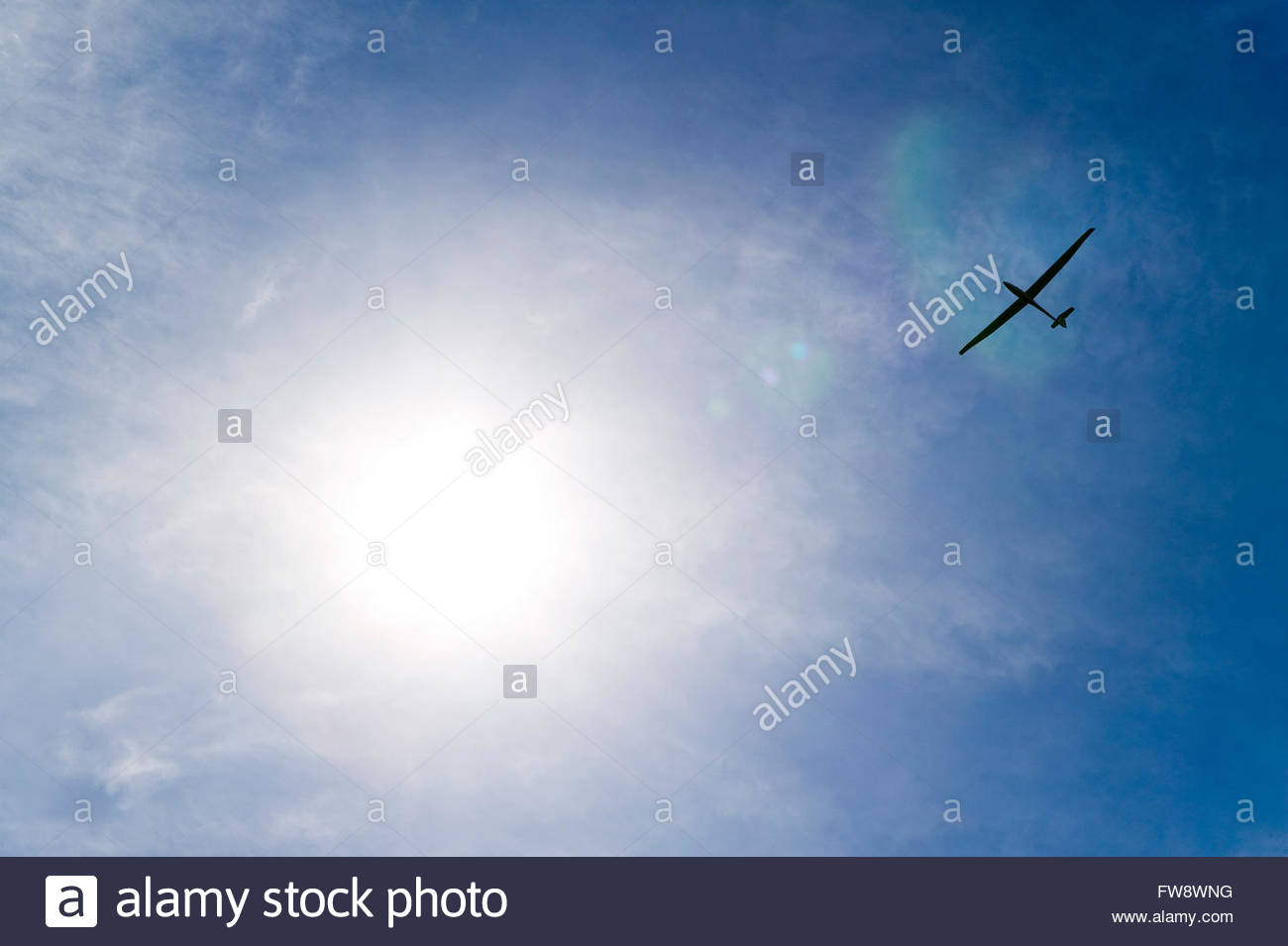 A glider soars above the ground and past the flare of the sun in a blue sky with small clouds, silently flying above - Stock Image