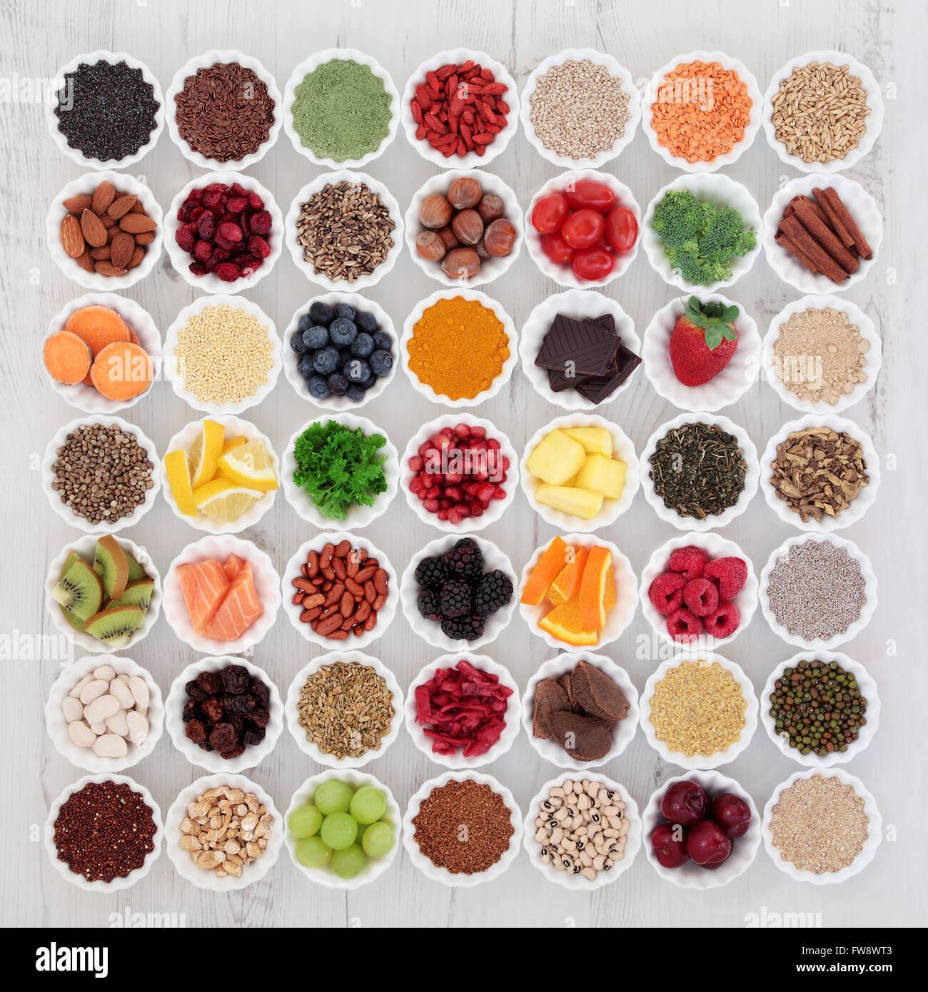 Large super food selection in porcelain crinkle bowls over distressed wooden background. High in vitamins and antioxidants. - Stock Image