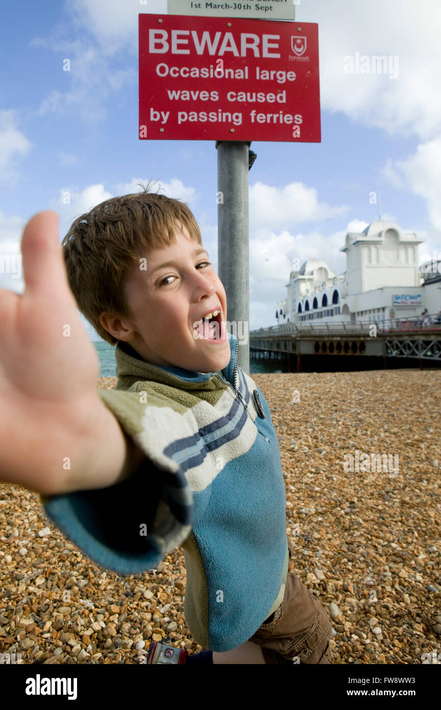 A young boy leans towards the viewer and makes a face while playing on the beach near toa  pier on the south coast - Stock Image
